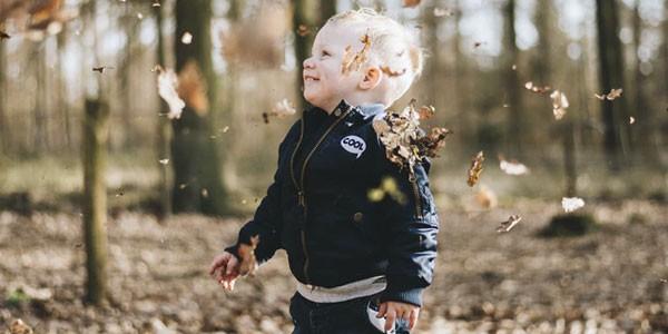 ragazzo saltando sulle foglie
